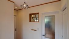 杜市高根町のかわいい家 玄関エントランスのかわいい照明と室内木製窓